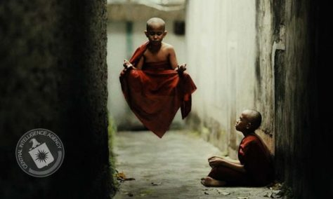 A photograph of two very young buddhist monks, showing one of them sitting in an alley while the other is seemingly levitating in front of him. The image is stamped by the Central Intelligence Agency.
