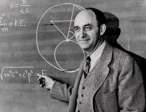 A photograph of physicist Enrico Fermi posing in front of a blackboard.