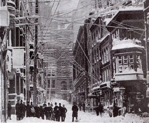 An old black and white photograph showing the aftermath of the historical blizzard in a street of New York City, with people gathered under the precariously tangled web of overhead electrical cables.