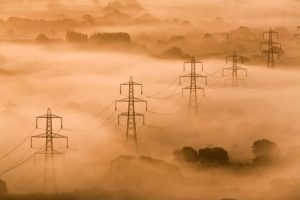 A photograph showing a series of five giant pylons emerging from the dense countryside fog.