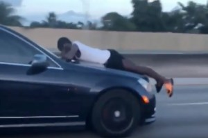 A man bonnet-surfing a car moving at speed, while trying to make a telephone call.