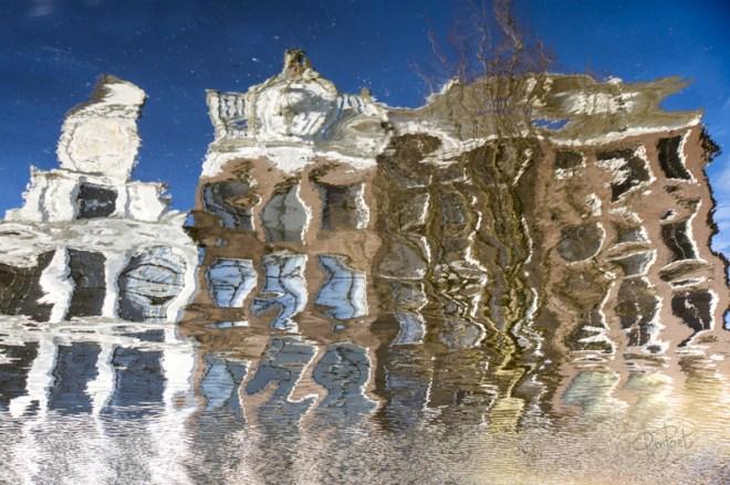 Spiegeling van grachtenhuizen in het water van een Amsterdamse gracht.