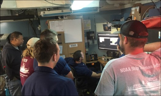 Members of the crew of the TJ look on as the HIC aboard the ship controls the launch remotely.
