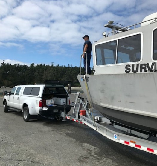 Lt. j.g. Joshua Fredrick on trailered survey response vessel.