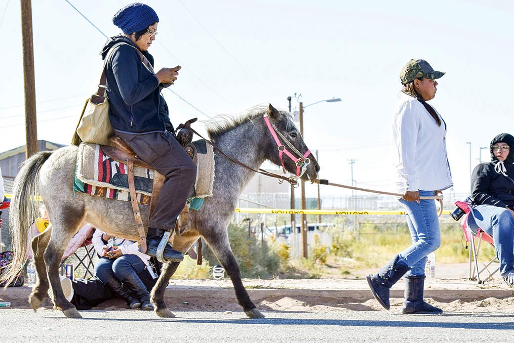 Navajo Times | Krista Allen A woman leads a miniature horse carrying a rider occupied with her cellular phone during the 49th annual Western Navajo Fair on Saturday morning.