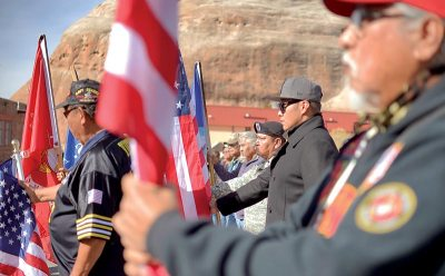 Veterans line up amid American and Marines flags.