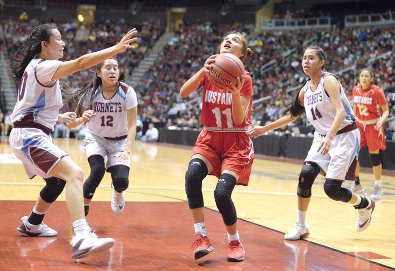 Navajo Times | Donovan Quintero Monument Valley Lady Mustang Briana Gillis (11) looks to shoot the ball before Ganado Lady Hornets Amber James, left, Jayla Mcintosh (12) and Janaya Mcintosh (14) block her Friday in Glendale, Ariz.