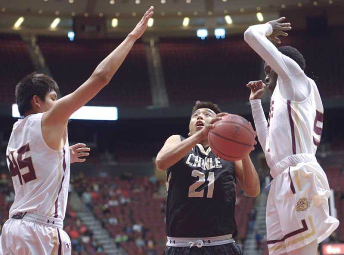 Navajo Times | Donovan Quintero Chinle Wildcat William Carroll (21) drives between guarding Winslow Bulldogs Zach Wagner, left, and Djassa Yoann on Saturday during the Arizona 3A boys semifinals at the Gila River Arena in Glendale, Ariz.