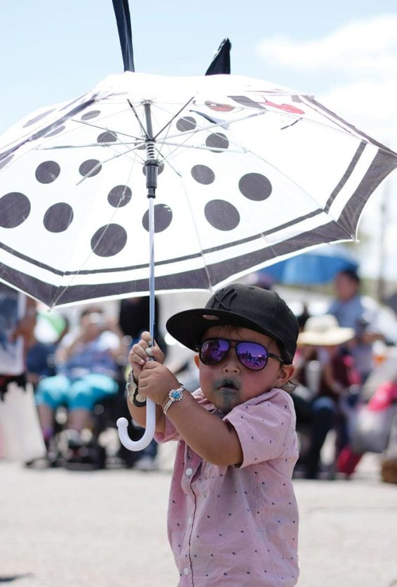Navajo Times | Ravonelle Yazzie Elliot Frank, 2, keeps himself cool with an umbrella and sunglasses in the Gallup Inter-Tribal Indian Ceremonial parade on Aug. 11.