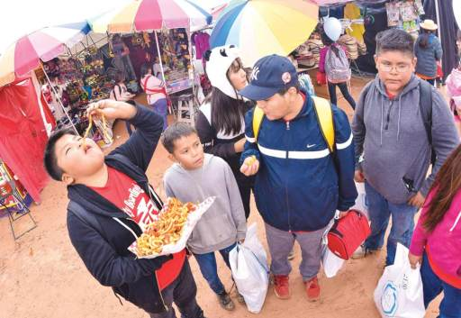 Navajo Times | Krista Allen Garland Yazzie from Tuba City Boarding School eats curly fries while standing with his friends during Kids Day at the 50th annual Western Navajo Fair on Oct. 11.