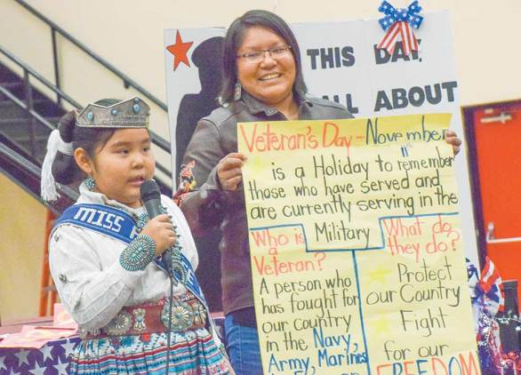 Navajo Times   Krista Allen Sheila Sells holds up a sheet, which gives the meaning of Veterans Day, for her daughter Kenzie, the Miss Peewee Kayenta Community School, as she makes a presentation at a Veterans Day ceremony at Monument Valley High in Tódinéeshzhee' on Nov. 12.