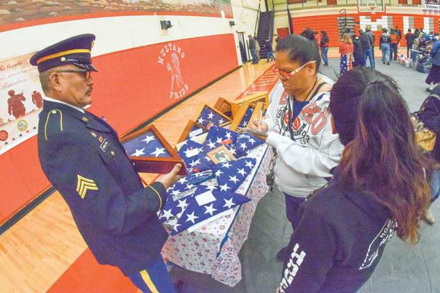 Navajo Times   Krista Allen A woman writes the name of her deceased loved one on a piece of paper while retired U.S. Army Sgt. Paulson Bronston holds an encased burial flag that was unfolded and refolded during a Veterans Day ceremony at Monument Valley High in Tódinéeshzhee' on Nov. 12.