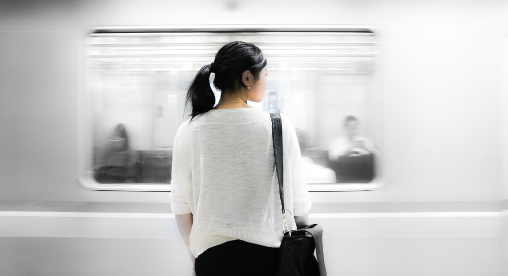 Woman standing in front of fast moving train