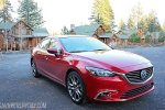 Picture of a cherry red Mazda 6 parked in front of cabins surrounded by trees.