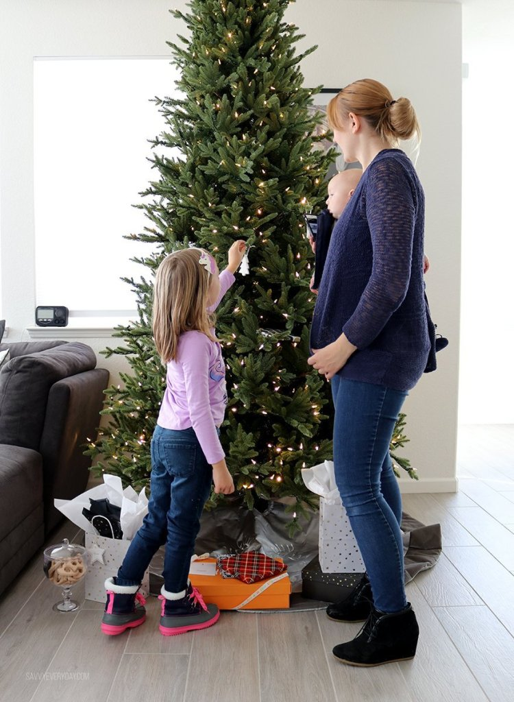 placing Christmas ornaments on the tree