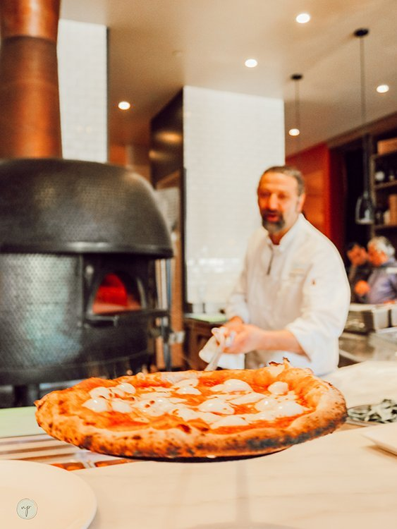 Trabocco owner Giuseppe Naccarelli shows pizza out of the fire