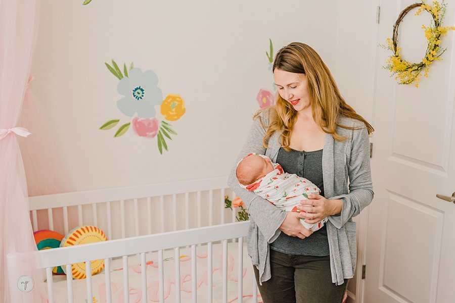 holding Nora in floral bohemian nursery
