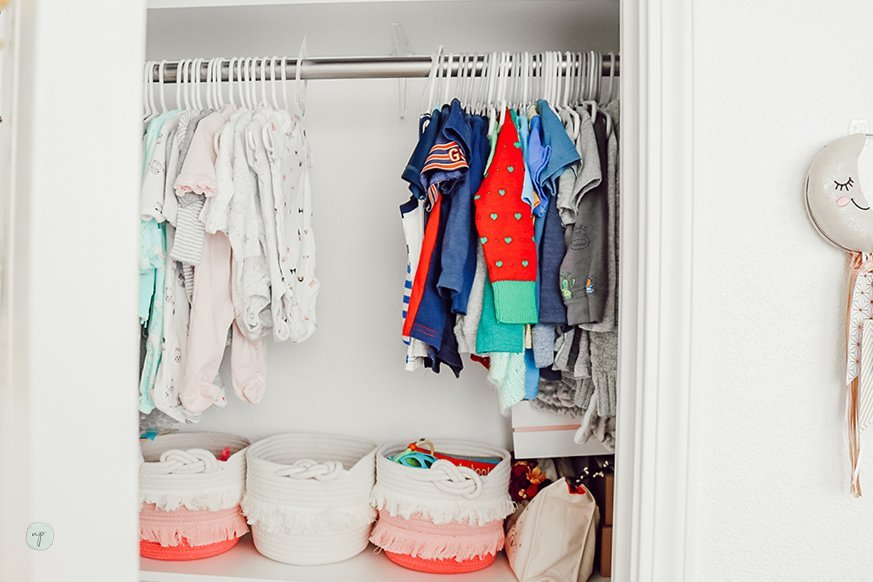 Photo of baby clothes hanging in a closet