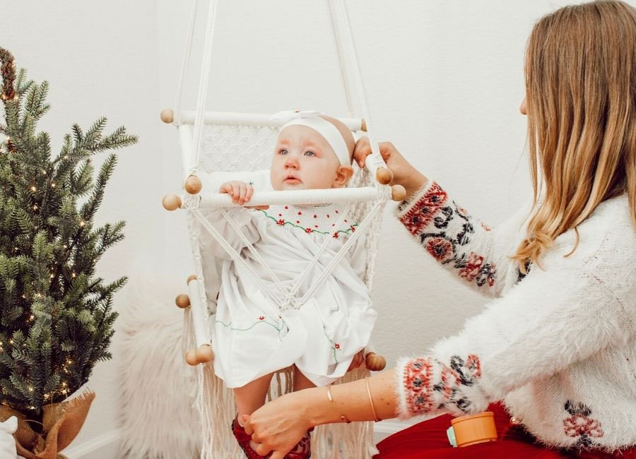 baby in macrame swing with mom holding the swing