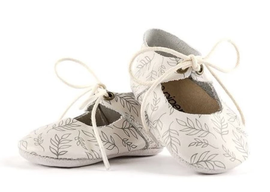 Cream soft sole shoes with grey leaves drawn on them and shoe laces