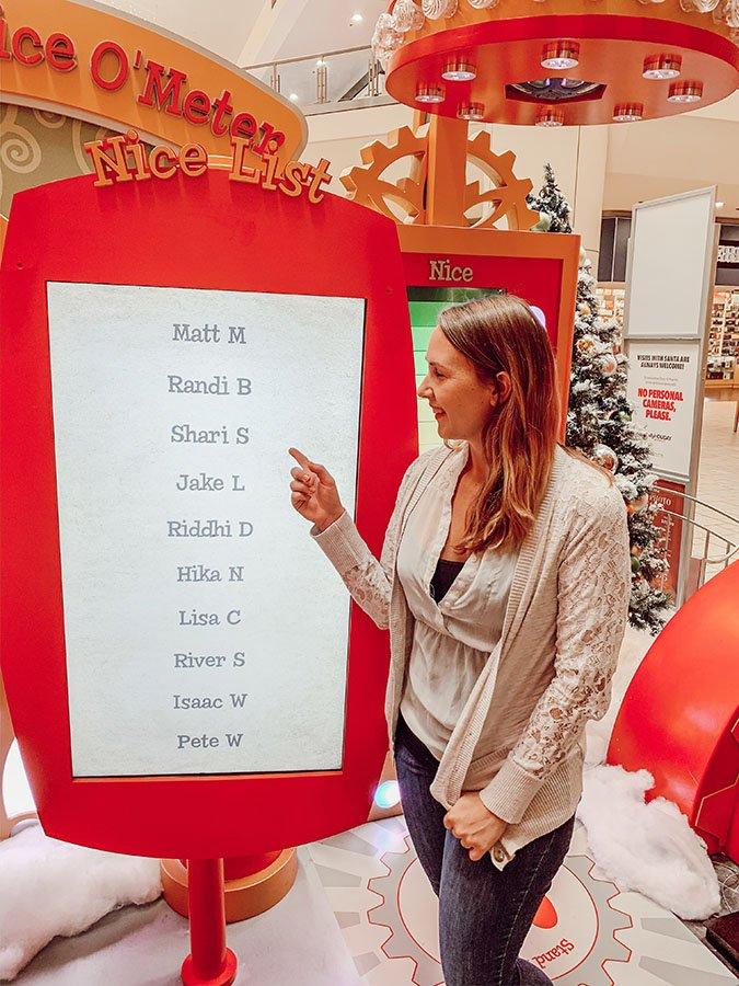"""Woman (Shari) pointing at a monitor called the """"Nice List"""" with a list of names on it to show that she's on the list"""