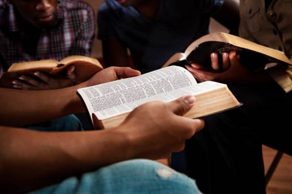 three people reading Bibles