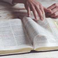 How To Memorize Scripture | The Navigators Bible Study Resources | hands paging through a bible on a wood desk