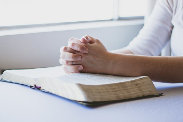 A Glorious Moment | Woman sitting with hands folded in prayer over a Bible