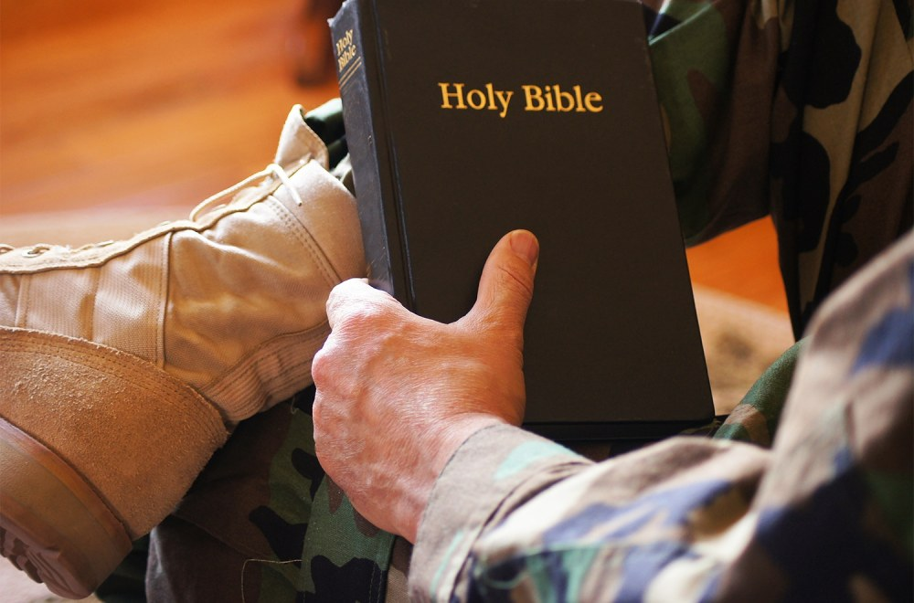 Soldier wearing camouflage clothes and military boots holding a Bible