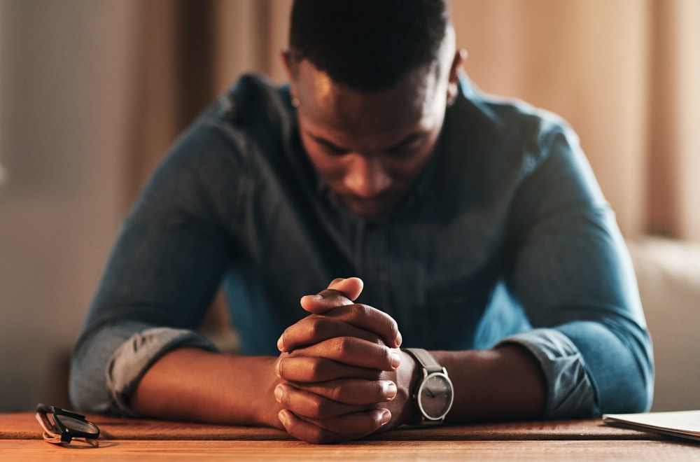 Overcoming Obstacles to Prayer: An Interview With Jarrett Stevens | The Navigators Navpress | young businessman sitting with his hands together in his home office and praying