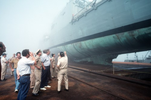 A crowd observes the damaged guided missile frigate USS SAMUEL B. ROBERTS (FFG-58) secured on the deck of the Dutch salvage ship MIGHTY SERVANT II.  The MIGHTY SERVANT II transported the frigate back to its home port after it struck a mine in the Persian Gulf on 14 April 1988.