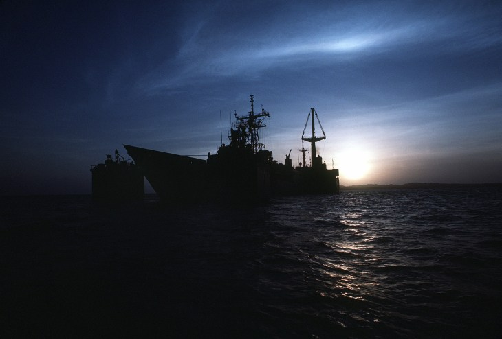 The guided missile frigate USS SAMUEL B. ROBERTS (FFG-58) is silhouetted by the setting sun as it is tranported on the deck of the Dutch heavy-lift ship MIGHT SERVANT II.  The MIGHTY SERVANT is transporting the frigate, which was damaged when it struck an Iranian mine on April 14, 1988, to its home port in Newport, R.I.