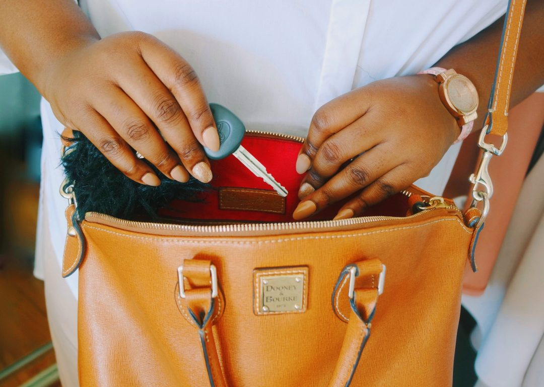 holding car keys to place into cognac purse