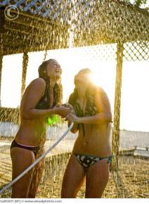 Teenage girls in bikinis playing in hose