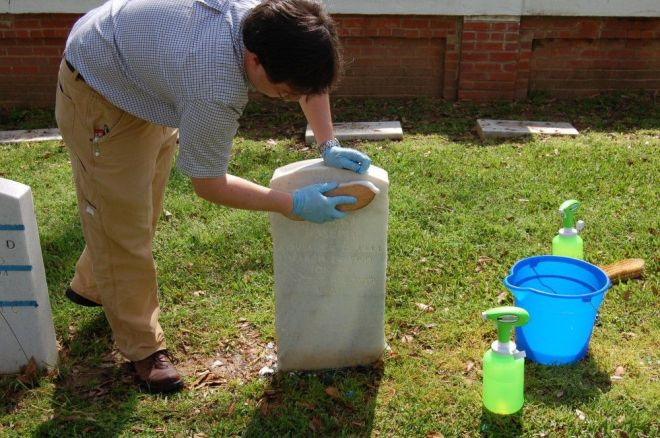 Jason Church demonstrating how to clean a monument
