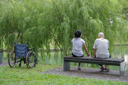 carer and man on bench outside