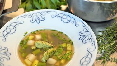 Clear asparagus soup with wild garlic dumplings served on a plate.  © NDR Photo: Florian Kruck