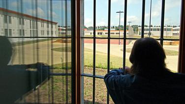 Ein Mann schaut durch ein vergittertes Fenster. © dpa Fotograf: Carsten Rehder
