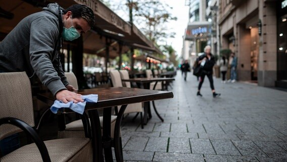 An employee wipes tables in front of a cafe in a city center.  © picture alliance / dpa / Fabian Strauch Photo: Fabian Strauch