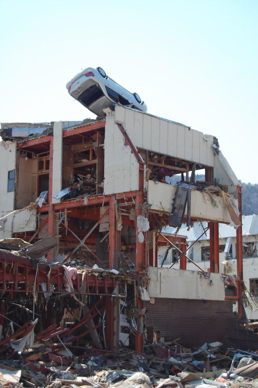 ビルの屋上で横転する車(女川町黄金町付近で撮影)