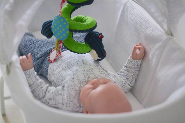 niemowlę w koszu mojżesza z zabawką
