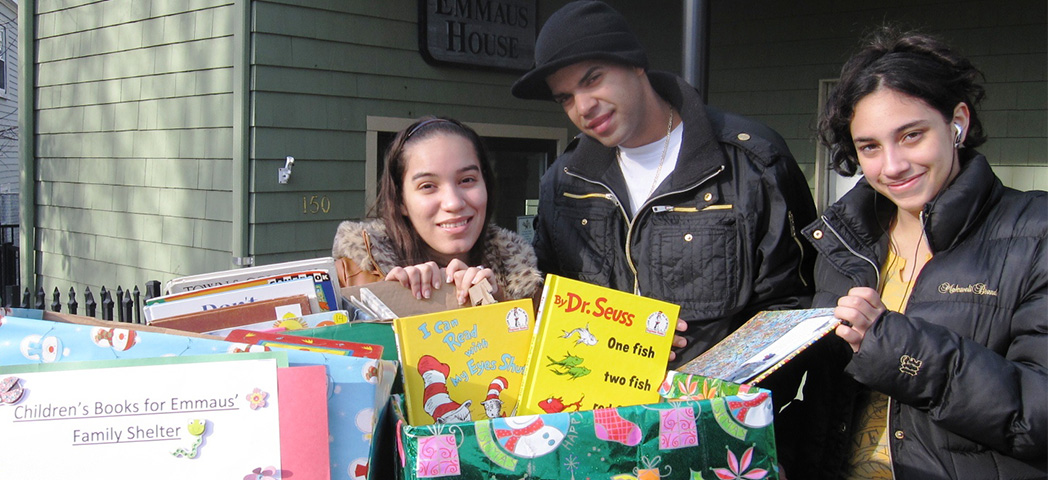 Three NECC students at Emmaus House with several large boxes of children's books.