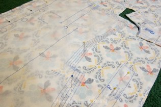 Laying out the fabric with the pattern, making sure the grainline is followed.