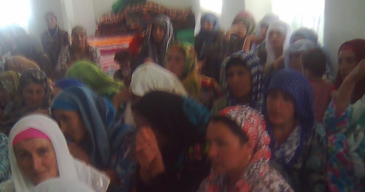 a blurry picture of a group of tajik women in colorful dresses and headscarves