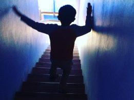 Child walking down a tunnel toward light.