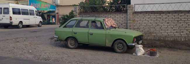 old car and a sleeping man