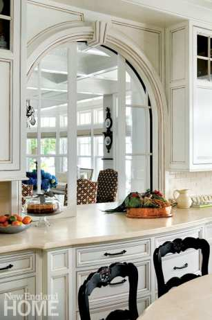 An arched pass-through with pocket doors makes for easy access between kitchen and dining room.