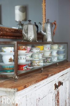 Dainty cups parading atop a rustic cabinet create a fun contrast.