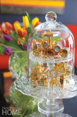 There's no doubt that Dragoo's collections are in great measure responsible for boosting the home's appealing personal vibe. Elevated on cake stands beneath a glass cloche, miniature clocks garner special attention.