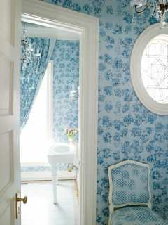 "The elegant powder room is swathed in blue floral fabrics. ""I wanted to make it a jewel box,"" says Griffin-Balsbaugh."
